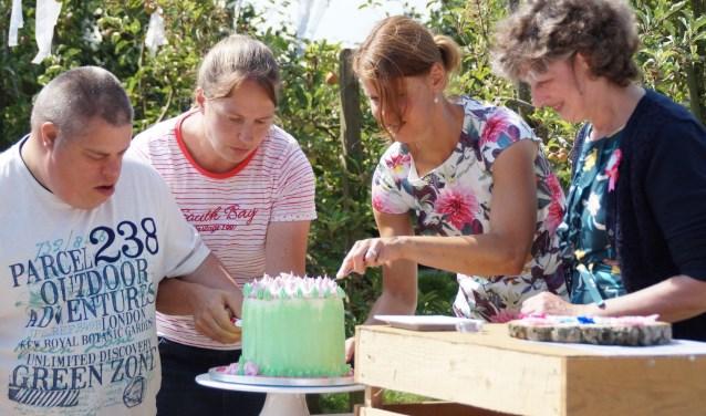 Een aantal cliënten en medewerkers sneden bij wijze van opening van theetuin Joostenshof in Waarder een kleurrijke taart aan. Foto: Picasa