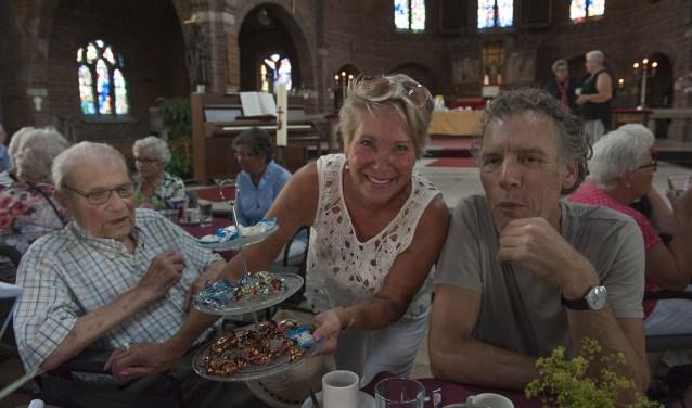 Jan Leijser krijgt wat lekkers aangeboden. Hij is met zijn zoon (rechts) bij het koffie-uurtje in de Zandse kerk. (foto: Ellen Koelewijn)