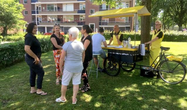 Bewoners en medewerkers van ContourdeTwern in gesprek terwijl aan de Koffiekar het verhaal van een koffiekop uit de buurt opgetekend wordt.