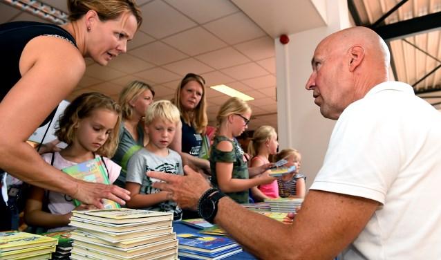 Fred Diks, schrijver van Koen Kampioen, praat met de moeder van Merle (7 jaar). Ze kocht drie boeken. (foto: Roel Kleinpenning)