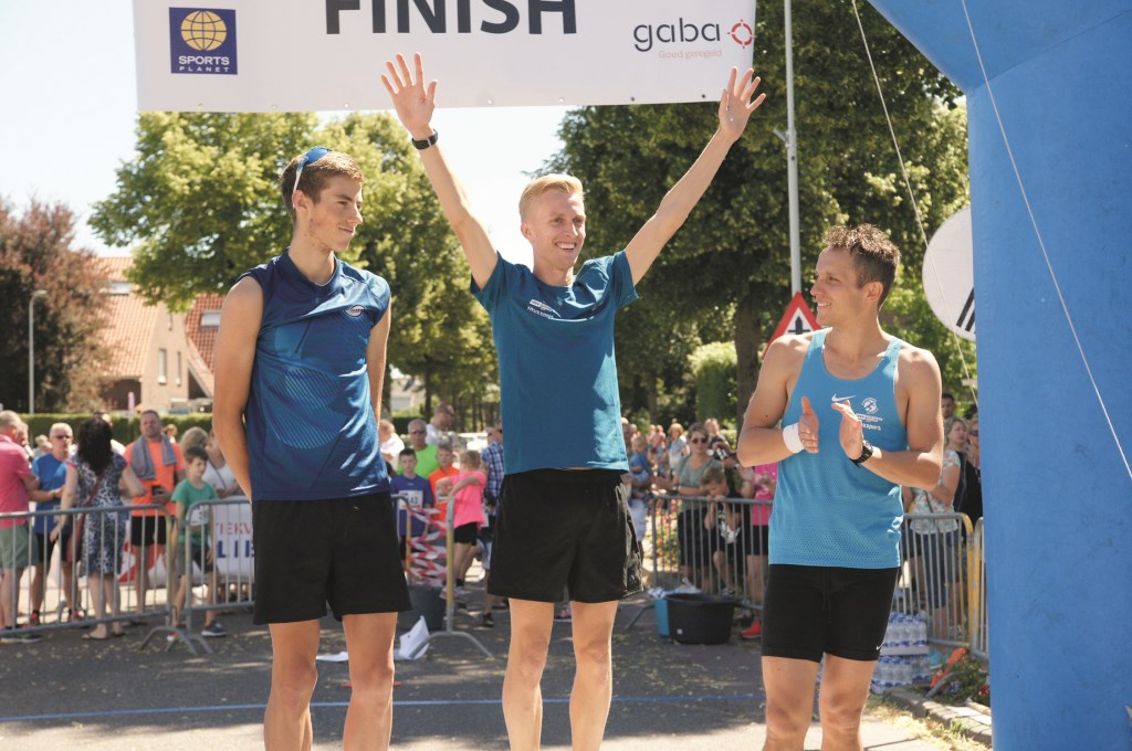 Frank Futselaar wordt gehuldigd als winnaar van de 5 kilometer. Tweede werd Thomas Cremers uit Elst (links) en derde Guido Engelen uit Zevenaar.