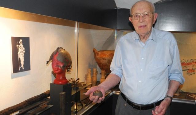 Vrijwilliger Frits Redeker toont een van de kogels, die in de vitrine in de kelder van het museum worden bewaard. Foto Voerman Museum Hattem.
