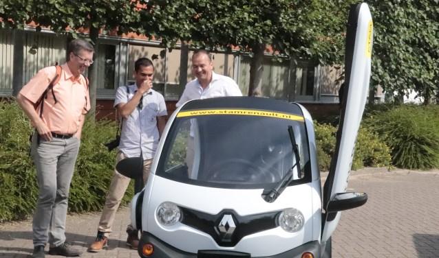 De wethouders Joost Reus en Collin Stolwijk bekijken een elektrische auto
