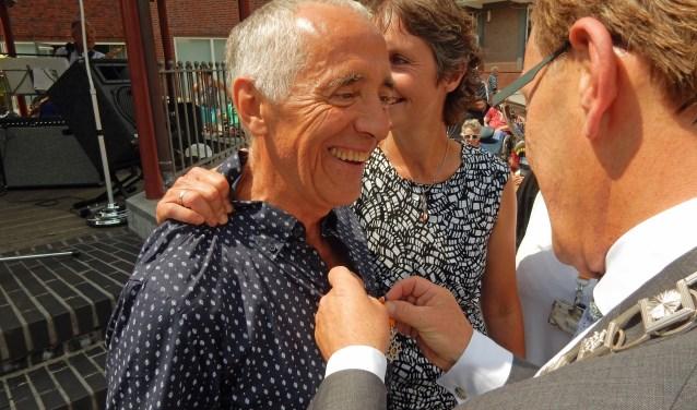 Beishuizen is zichtbaar verrast als burgemeester Koos Janssen hem de onderscheiding van Lid in de Orde van Oranje Nassau opspeldt. Zijn vrouw Mirjam de Lang is net zo blij als haar man. FOTO: Asta Diepen Stöpler