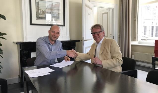 Wethouder Auke Schipper (l) en Dick Stoppelenburg ondertekenden de overeenkomst voor zonnepanelen op de gymzaal aan de Spoorstraat