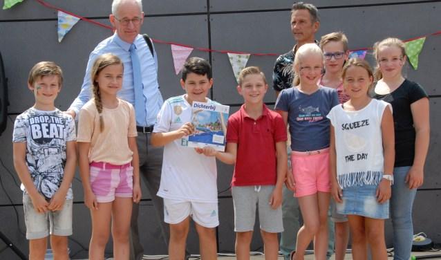 Leerlingenraad neemt Dichterbij in ontvangst van Henk Bolt. Meester Jaap kijkt tevreden toe.