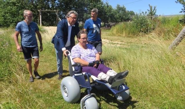 Wethouder Rob Engels duwt Lia over een struinpad op Landerij de Park