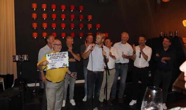 Voorzitter Wilbert van Herwijnen van stichting Alegria krijgt de cheque aangeboden door de wielrenners. Zij gaan in september de Mont Ventoux beklimmen.