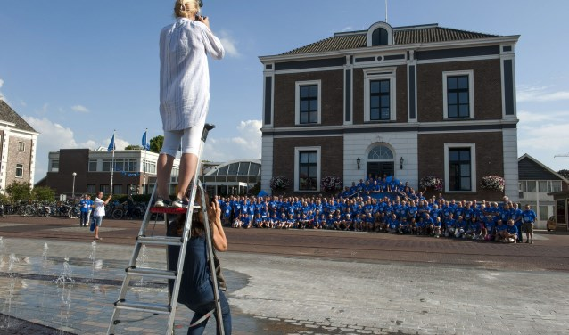 Suzanna Kolenbrander neemt voor het gemeentehuis in Elst een foto van alle Vierdaagselopers uit Overbetuwe. (foto: Ellen Koelewijn)