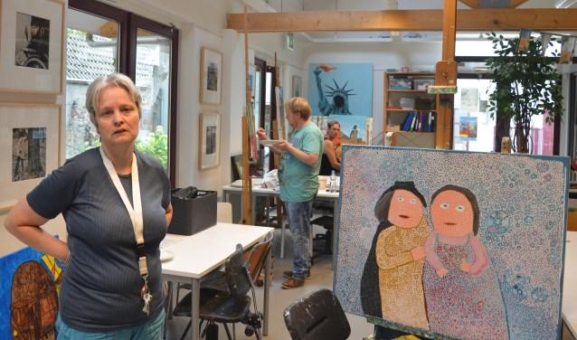 Marieke Romeijn poseert bij recent werk, terwijl collega's René en Louis hun schilderijen vervolmaken. FOTO: Ben Blom