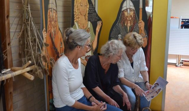 Het educatief team van Museum Dorestad bespreekt het boekje vlnr Leny Janoz, Resi Enzlin en José van der Lee. Ze zitten in de Vikinghoek van het tijdelijke museum. Foto: Ben Blom