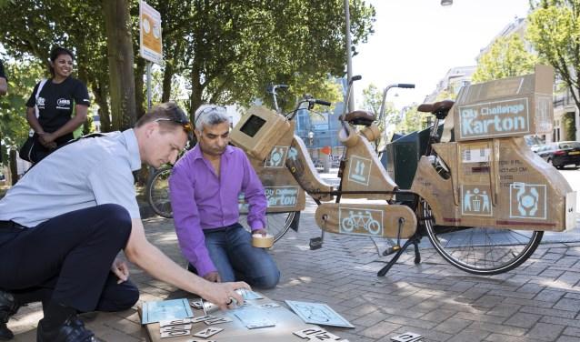 Juryleden Frank Kanhai en Cliff Nijssen geven het startsein voor de City Challenge Karton, waarmee de gemeente op zoek gaat naar  ideeën om het scheiden van karton makkelijker te maken. (Foto: Inge van Mill)