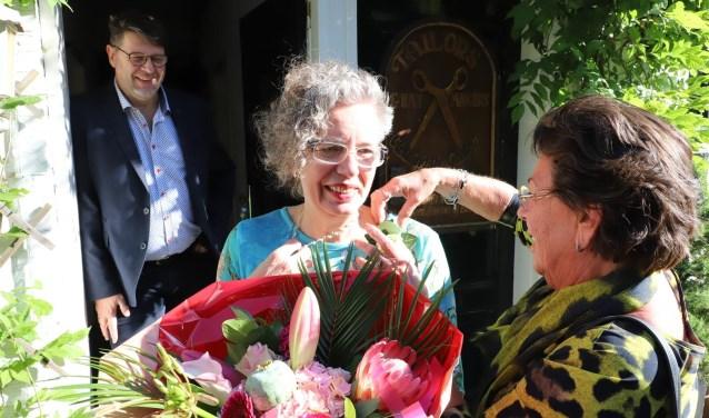 Jubilaris met bloemen en corsage