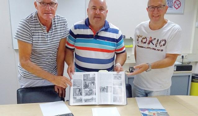 De bestuursleden (vlnr) Piet Dorst, Donald Smakman en Gert Gravendeel bij een boek over de fabrieksgeschiedenis en een aantal kalenders. (foto: Koos Romeijn)