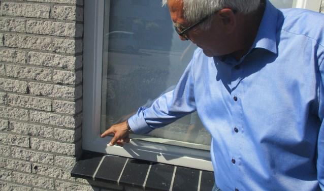 De Nooijer toont schade aan het raamkozijn veroorzaakt door de hitte. FOTO: MARCEL VAN DER VOORT.