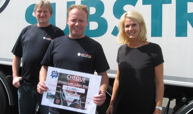 Johan Blom (midden) kreeg uit handen van Petra Hooymans (rechts) van Hooymans Substrates uit Velddriel een cheque van 1000 euro voor hun deelname aan de Amsterdam City Swim.