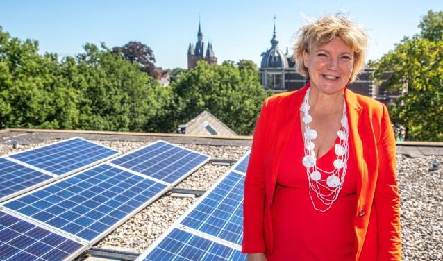 Wethouder Monique Schuttenbeld op dak Stadskamer met zonnepanelen en uitzicht op de Sassenpoort.