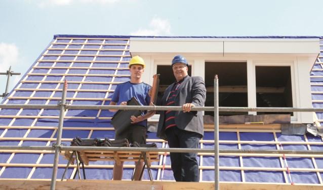 Wethouder Hans Sluiter (rechts) en bouwvakker Thijs Koens leggen samen de eerste dakpannen op een van de huizen in de nieuwe wijk Beekenoord.