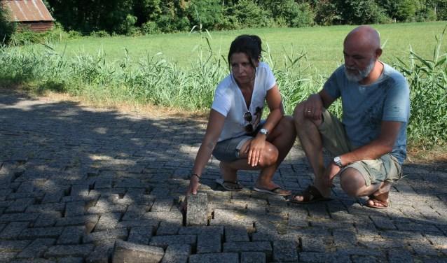 De bewoners laten zien wat ze bedoelen. Losliggende stenen worden uit het wegdek gereden en de weg is flink verzakt.