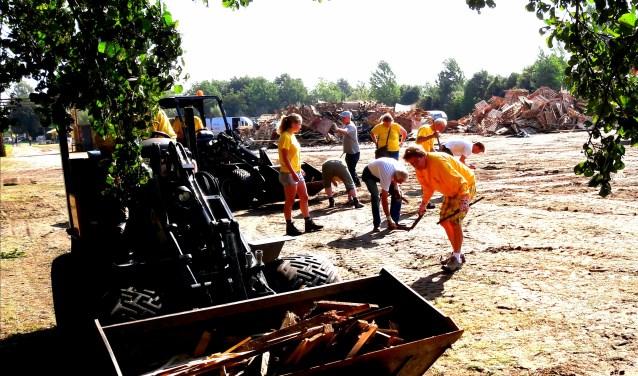 De grote gele machines doen het ruige werk, de bikkels van het Kinderdorp rapen splinters en spijkers en leveren het huttendorpterrein weer schoon op.