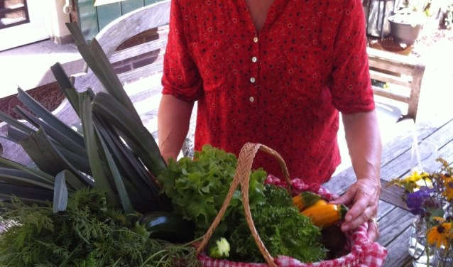 Jose Ras uit Laren reageerde enthousiast op Willem's oproep voor recepten met courgettes. Ze stuurde ons zowel een wok- als een ovenrecept. Op de foto neemt ze als dank een tas groente in ontvangst.