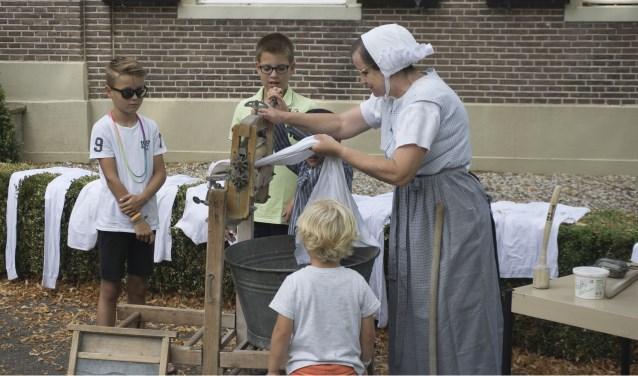 De dames van de Folkloregroep Riessen laten jeugdige bezoekers zien hoe vroeger de was door wringer werd gehaald. Foto: Albert Last.