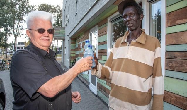 Joop van Ommen deelt flesjes water uit de bewoners van de Herberg vanwege de aanhoudende warmte. (foto: Frans Paalman)