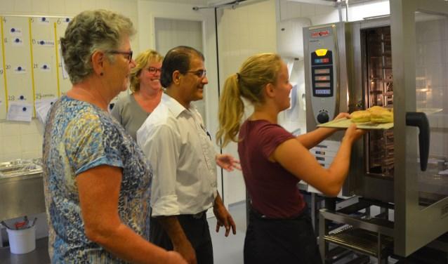 Liesette laat zien hoe de combi-oven werkt, daarbij op de vingers gekeken door Wil (l) en haar collega's Marianne en Koeresh. FOTO: Ben Blom