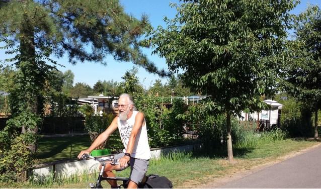 Peet Meijer fietst over het volkstuinencomplex. Zaterdag 18 augustus wordt het jubileumfeest gevierd.