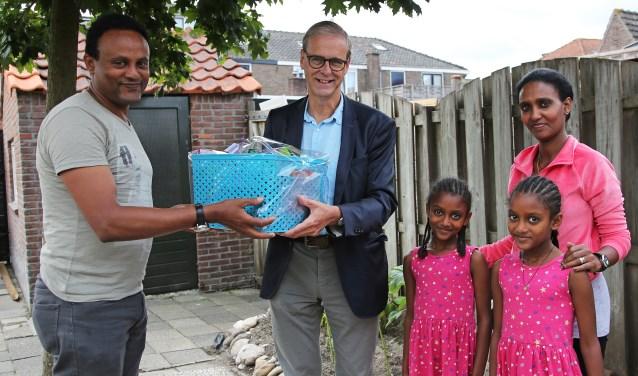Wethouder de Weger overhandigde een pakket bij een Eritrees gezin dat een aantal maanden in Woerden woont. Foto: Alex de Kuijper