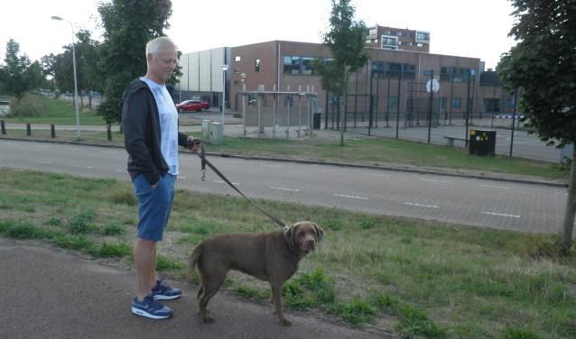 Bewoner Ed houd zijn labrador Gina aan de lijn bij sporthal de Ackers. Foto: Kees van Rongen