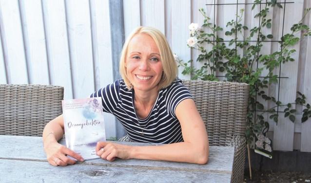 Chantal van Aken met de bundel 'Droomgedichten', waarin haar winnende gedicht staat afgedrukt.