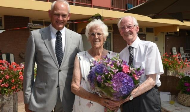 Burgemeester Lamers met het briljanten echtpaar Assendorp-Stolk en hun bloemen.