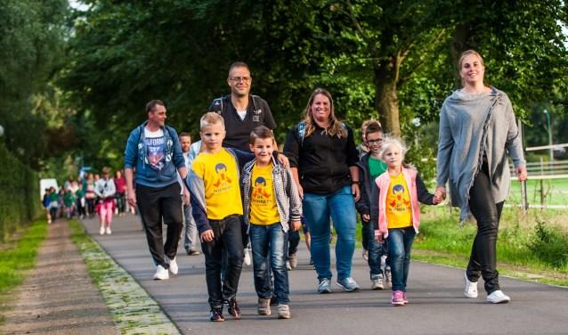 Wandelaars lopen gezellig samen de Avondvierdaagse. De organisatie hoopt dit jaar met de extra afstand de deelnemersgrens van duizend te doorbreken.