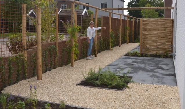 Bestuurslid Annelies Huffmeijer wijst naar de hoek waar de omheining al haar definitieve vorm heeft. De tuin wordt in de komende week afgewerkt. Iedere kamer heeft zijn eigen beschutte plekje en terras.