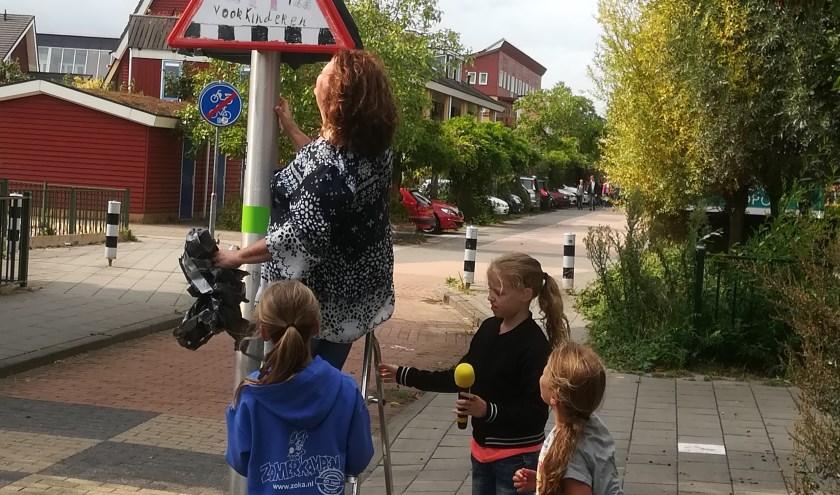 Directeur en leerlingen onthullen verkeersbord. Gepaste trots op het schoolplein van Jenaplanschool Praathuis in Culemborg.