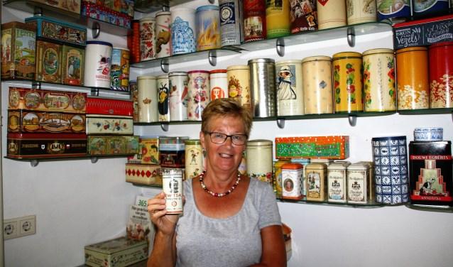 Henny in haar keuken tussen de beschuitbussen en met haar oudste blik in haar hand. FOTO: Astrid van Walsem
