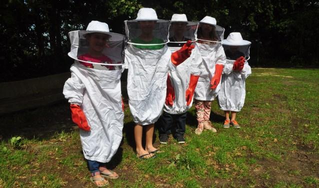 De imkers van bijenhoudersvereniging de Wal van Brabant brengen tijdens de kleutermiddag over bijen op woensdag 15 augustus bij de Kraaijenberg voor de kinderen ook imkerpakken mee. FOTO: LEO DEN HEIJER