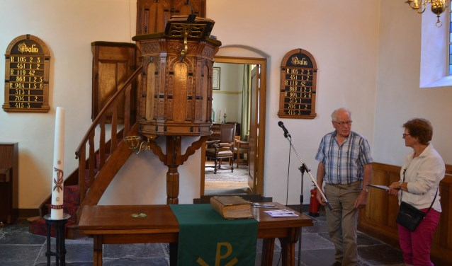 Vrijwilliger Pleun Nell legt aan passante Agnes Vernooij de inrichting van de kerk uit. De open deur gunt ons een blik in de consistorie.