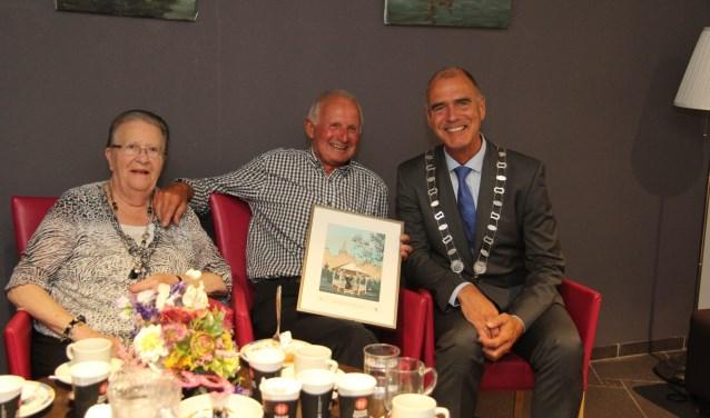 De heer en mevrouw Van Veenendaal zijn blij verrast door de komst van loco-burgemeester Kees van Dalen. (Foto Jan-Peter Geertman)
