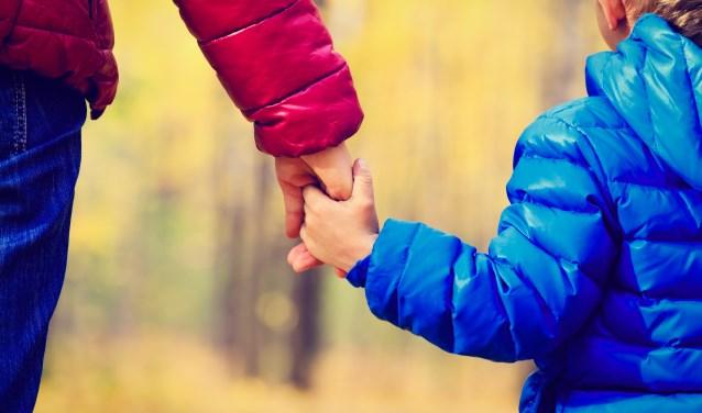 ouder en kind houden elkaars hand vast