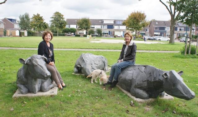 """Het Zegveldse kunstwerk Drie Koeien met kunstenaar Elselien van der Graaf (r) en Marita Damen: """"Fiets eens langs, al die kunstwerken, kijk wat het is. Met de QR-code willen we mensen meer bij de beelden betrekken."""""""