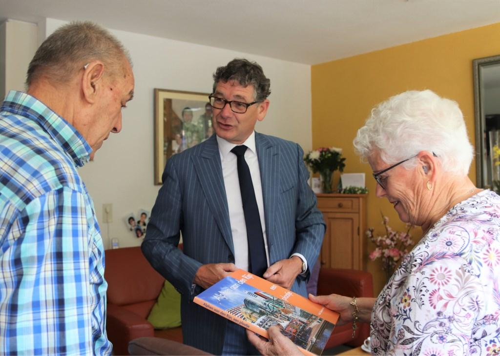 Wethouder Kees van Velzen feliciteert het echtpaar Van den  Wijngaarden-Vissers en overhandigt hen een cadeau. Foto: Esmeralda Wybrands © Persgroep