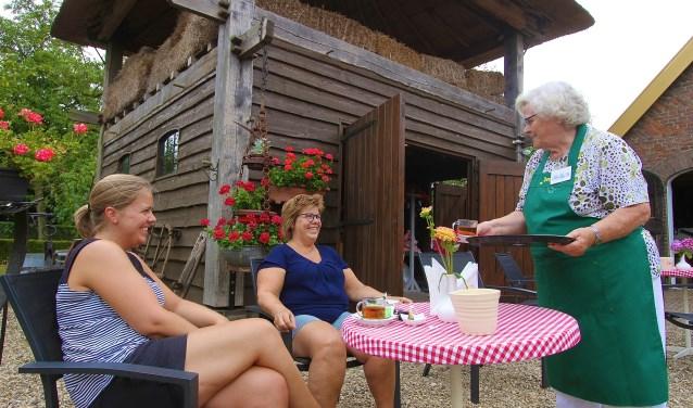 Dinie Franssen serveert de thee bij museumboerderij Den Tip aan  Nienke Haverhals (links) en Marga Repke. (foto: Kirsten den Boef)