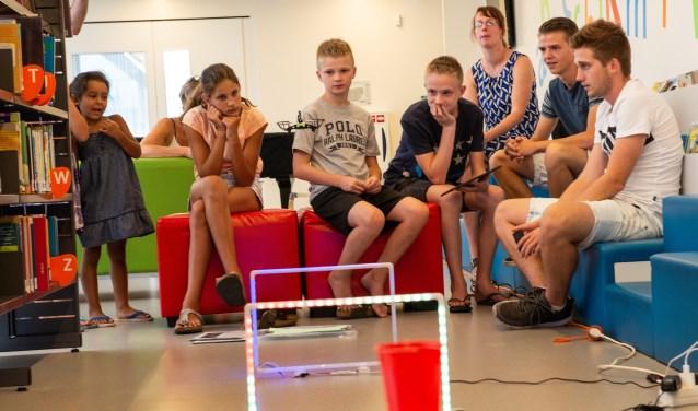 Jordy en Tim (rechts op de foto) van FutureMindz verzorgen in de bibliotheek in Heerde een informatiemiddag over drones. Foto: Dennis Dekker