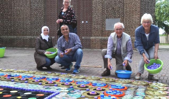 Ria en Kees en Andaleeb en Toufik werken aan het Tapijt voor Vrede. Achter: Marianne van Heeswijk. (Foto: Marco van den Broek)