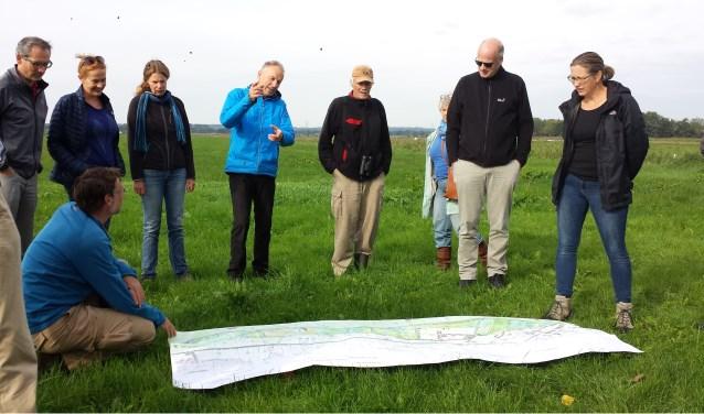 Certificaathouders krijgen uitleg van Rob Janmaat (in blauwe jas) over de plannen voor nieuwe natuur tijdens de excursie door het Binnenveld.