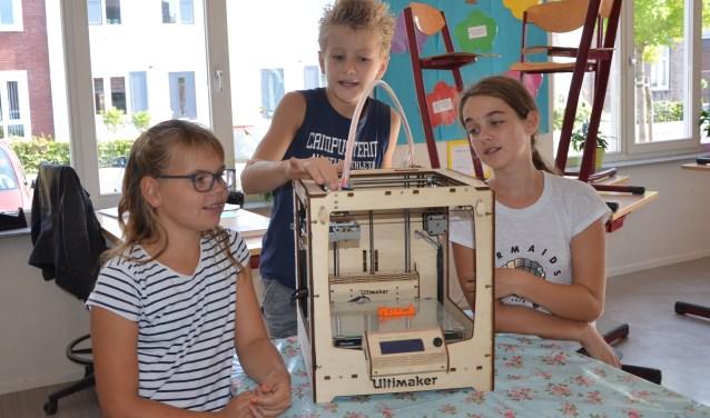 Nienke (l), Jorge en Ashlee hebben vorig jaar samen met anderen in groep 7/8 van OBS Piet de Springer een 3D printer in elkaar gezet. Hiermee hebben ze al naamplaatjes en handvatten gemaakt. FOTO: Ben Blom