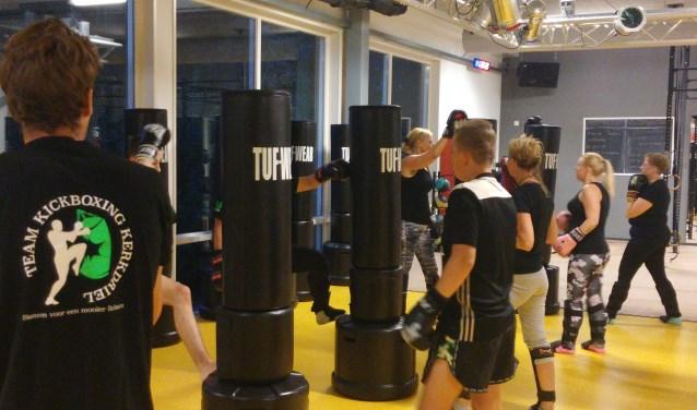 Voluit trappen en slaan tegen een bokspilaar. Cursisten van Team Kickboxing Kerkdriel verbeteren zo hun motoriek, conditie en lichaamshouding.