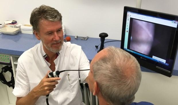 KNO-arts Kruit bekijkt via de neus met een minuscuul cameraatje de stembanden op een beeldscherm.